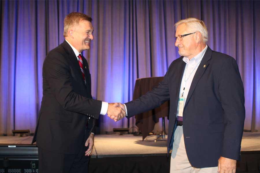 Bob Kran receiving shaking hands with Jim Mattheson